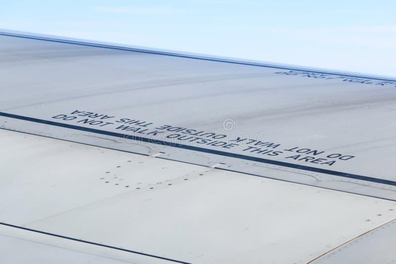 Mot de précaution sur l'aile d'avion images libres de droits