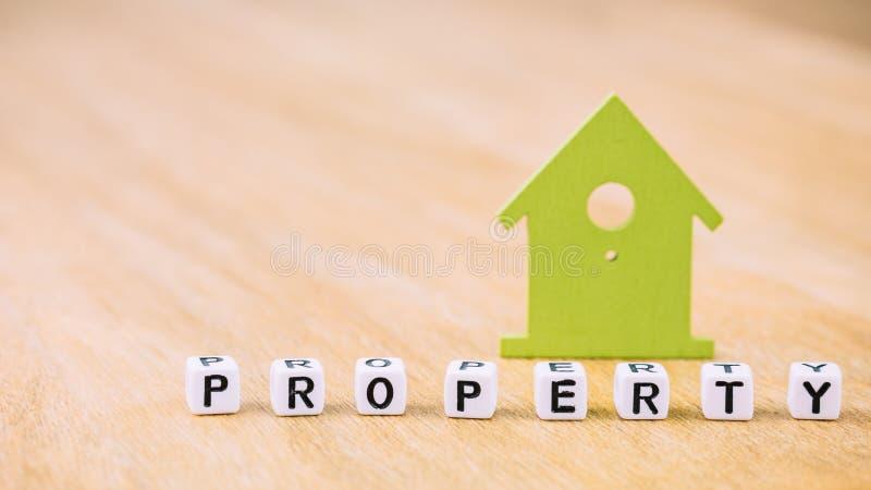 Mot de PROPRIÉTÉ des lettres de cube devant le symbole de maison verte sur la surface en bois Concept photos libres de droits
