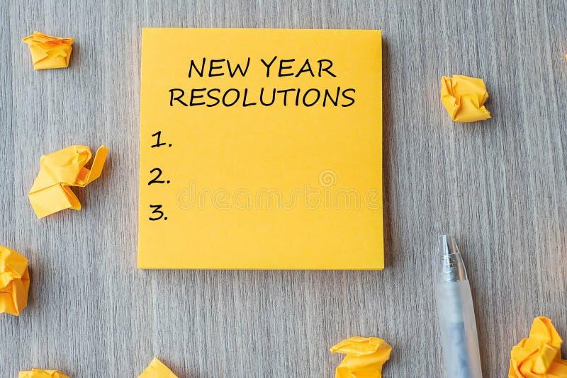 Mot de RÉSOLUTIONS de NOUVELLE ANNÉE sur la note jaune avec le stylo et le papier emietté sur le fond en bois de table Nouveaux d photos stock