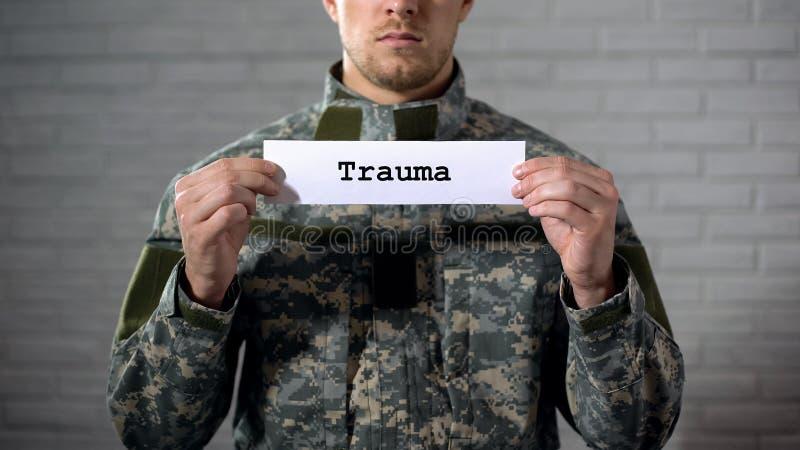 Mot de traumatisme écrit sur les mains de signe dedans du soldat masculin, dommages au corps, santé image libre de droits