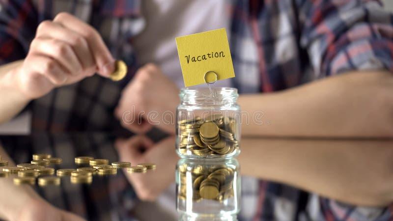 Mot de vacances écrit au-dessus du pot en verre avec l'argent, l'épargne pendant des vacances d'été images libres de droits