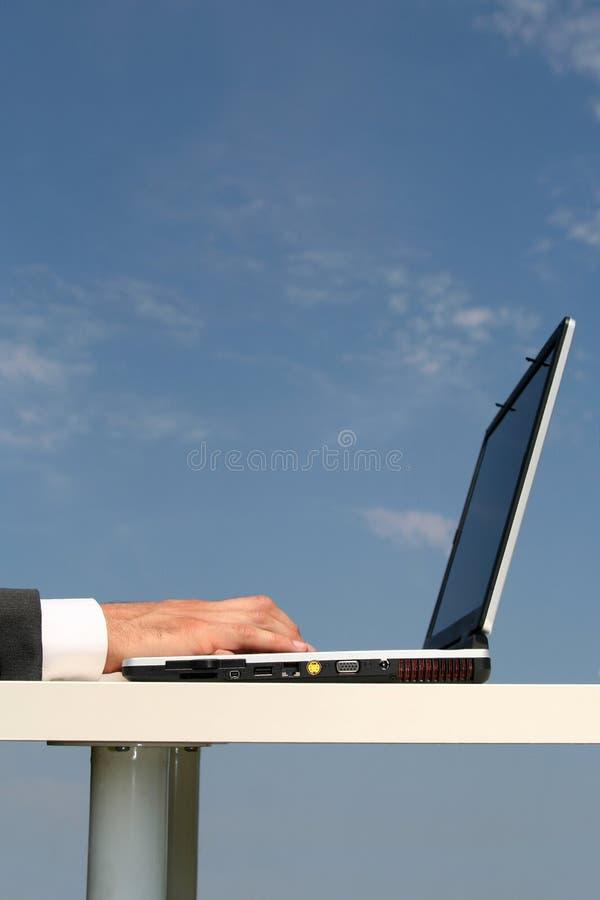 mot den blåa bärbar datorskyen arkivbilder