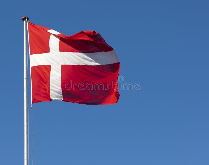mot den blåa danska dannebrogflaggaskyen arkivfoton