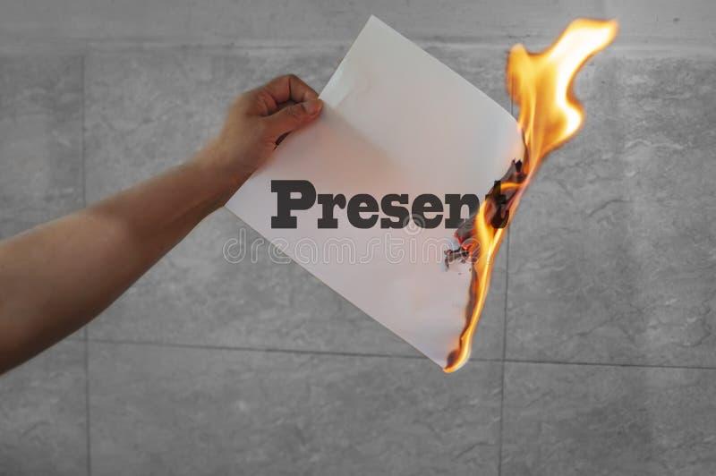 Mot des textes de l'époque actuelle brûlant sur le feu avec le papier photographie stock