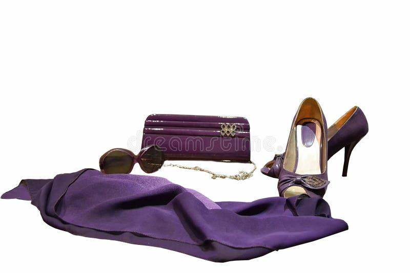 Mot en vit bakgrund purpurfärgade objekt för kvinna` s, koppling för kvinna` s arkivbild