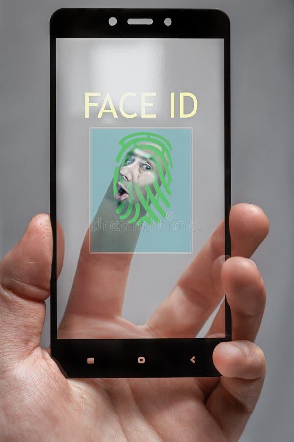 Mot exponeringsglaset trycks på en mänsklig framsida för biometric telefontillträde begreppet av personligt dataskydd arkivbild