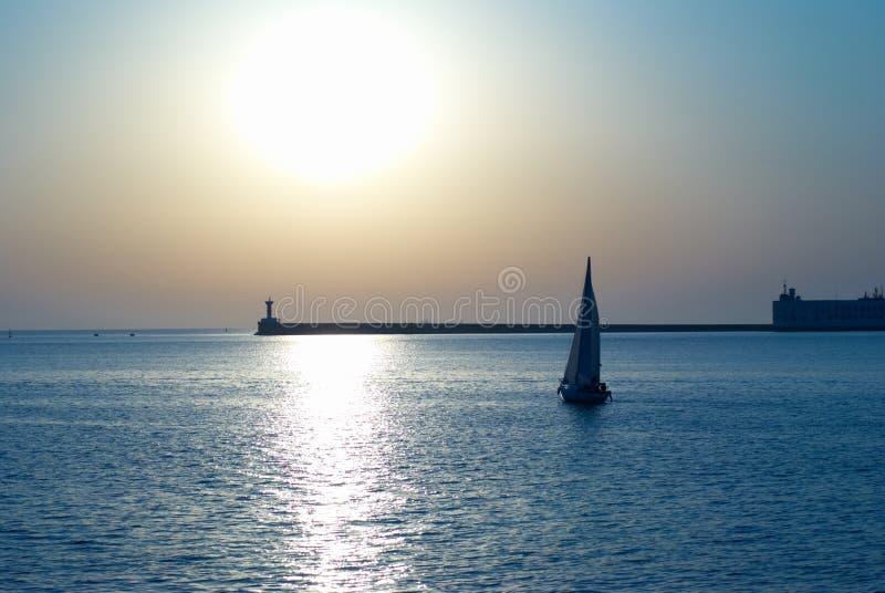 mot fartyget segla solnedgången arkivfoto