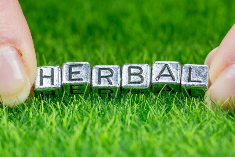 Mot HERBAL écrit en lettres métalliques posées sur l'herbe et tenues entre les doigts d'une femme Concept du contexte sanitaire photos libres de droits