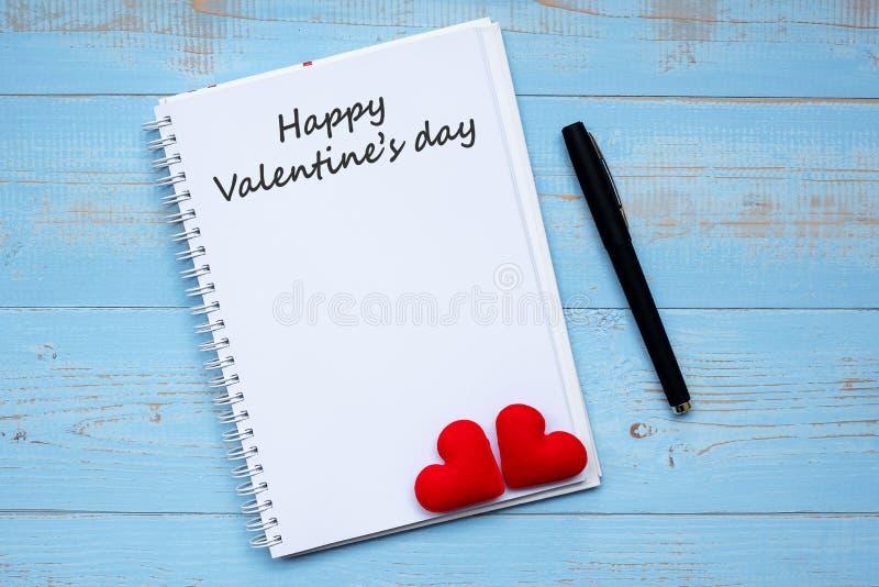 Mot HEUREUX de SAINT-VALENTIN sur le carnet et le stylo avec la décoration rouge de forme de coeur de couples sur le fond en bois image stock
