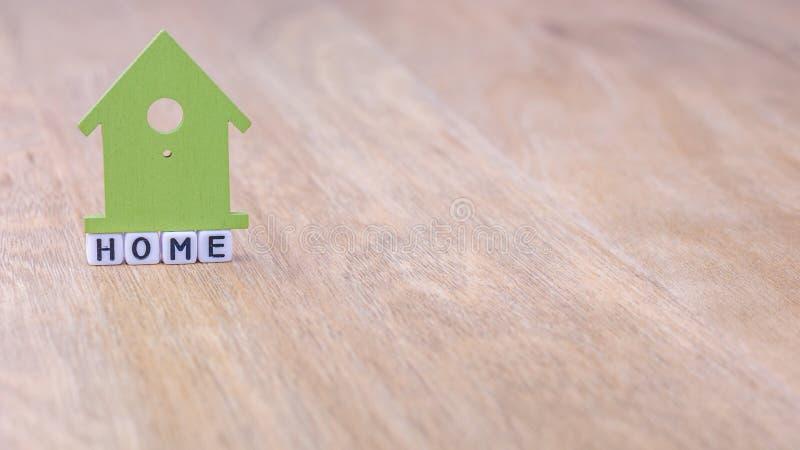 Mot horizontal À LA MAISON des lettres de cube avec le symbole de maison verte ci-dessus sur la surface en bois photos libres de droits