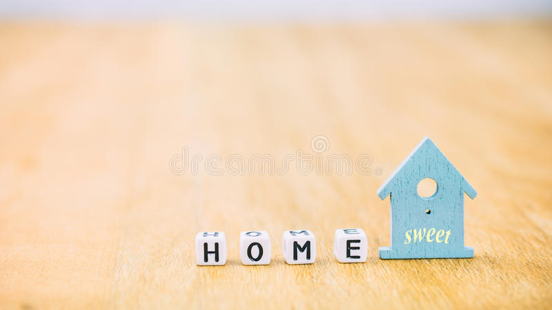 Mot horizontal doux À LA MAISON des lettres de cube derrière le symbole bleu de maison sur la surface en bois images stock