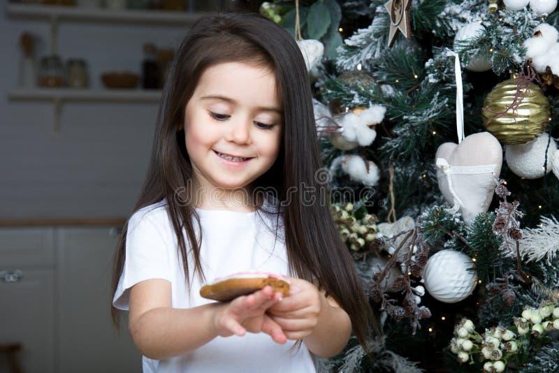 Mot julgranen en stående av lite flickan royaltyfri bild