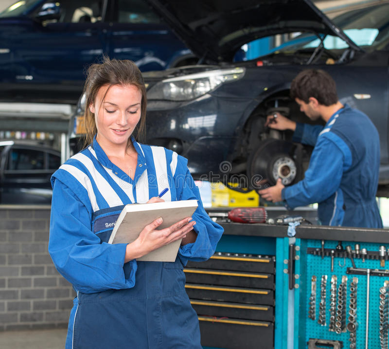 MOT Test and mechanics. Two mechanics, working in a garage on a MOT test of a car, with a female mechainc in front, checking off inspection items on a note block stock images