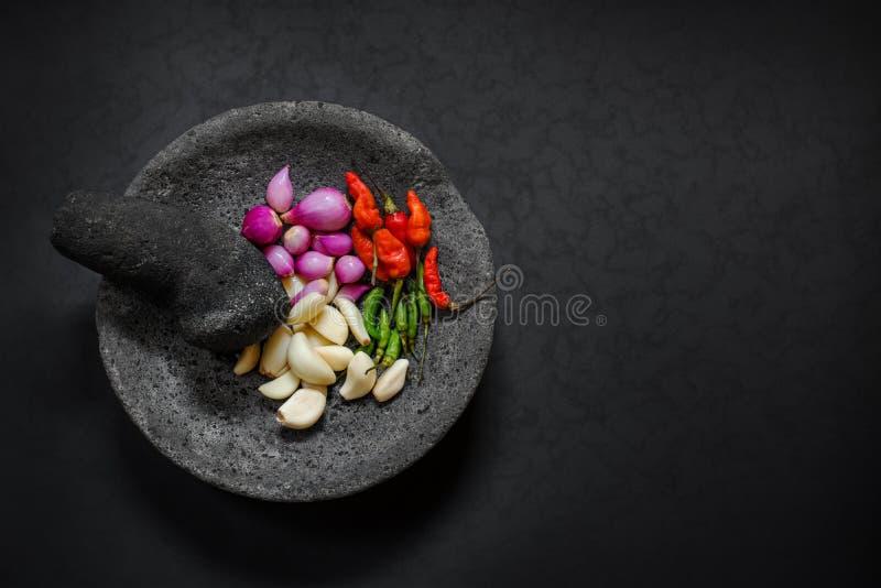 Motar de piedra tradicional y maja de Asia con el ingrediente picante imagenes de archivo