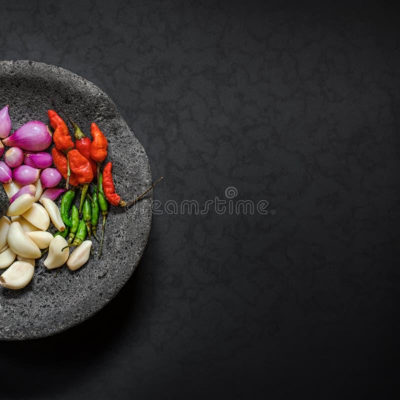 Motar traditionell sten & mortelstöt från Asien med den kryddiga ingrediensen royaltyfri fotografi