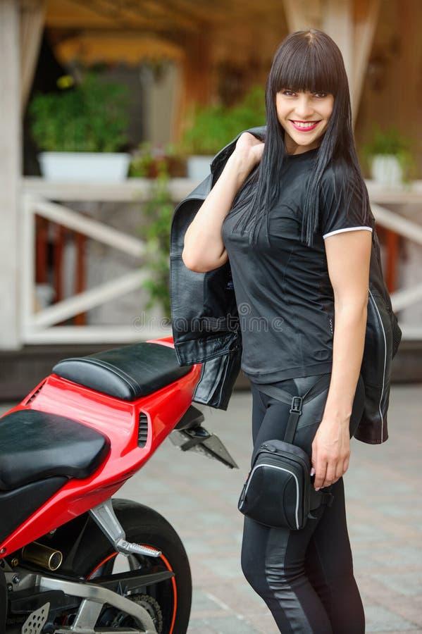 Motard de fille dans des vêtements noirs sur une moto de sports posant dans la ville image libre de droits