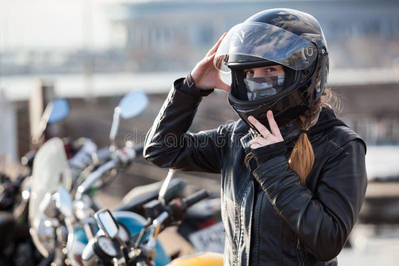 Motard de jeune fille essayant le casque noir de moto pour le tour sur le vélo images stock