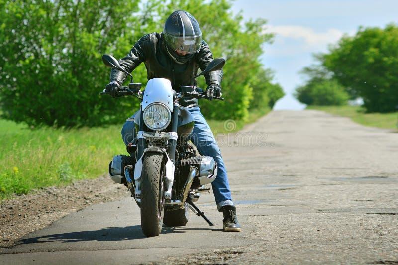 Motard de Moto et sa moto sur la route goudronnée Commencer à aller photos stock
