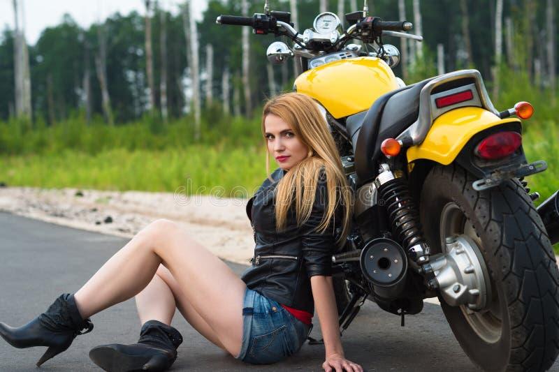 Motard sexy avec du charme de femme s'asseyant sur l'asphalte avec la moto photo libre de droits