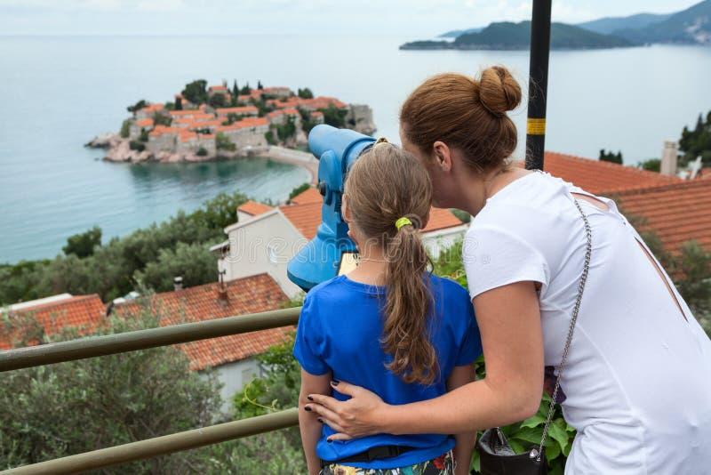 Moter i córka patrzeje Sveti Stefan wyspę Adriatycki morze, Montenegro, Europa Obserwować miejsce z moneta działającym telesc zdjęcie stock