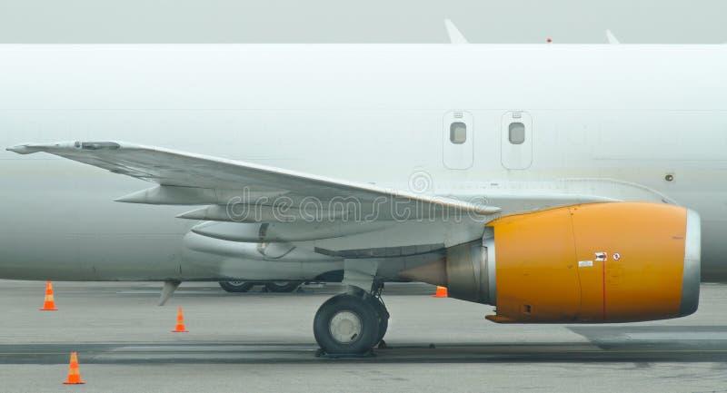 Moteur à réaction sur une aile de l'avion blanc images stock