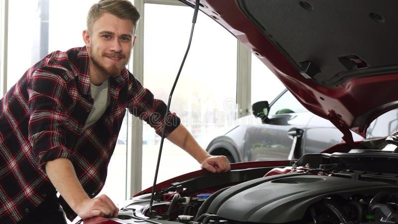 Moteur de examen de cutomer masculin beau d'une voiture à la salle d'exposition de concessionnaire photographie stock
