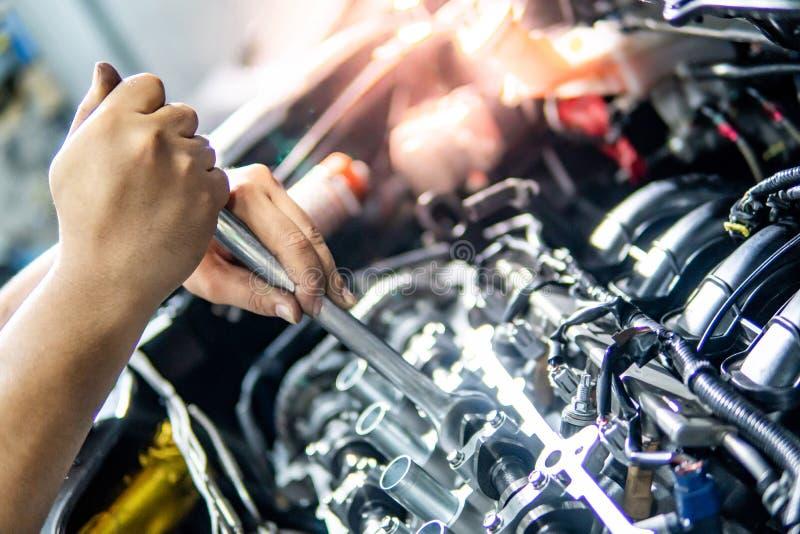 Moteur de voiture de fixation de main de mécanicien automobile dans le garage image stock