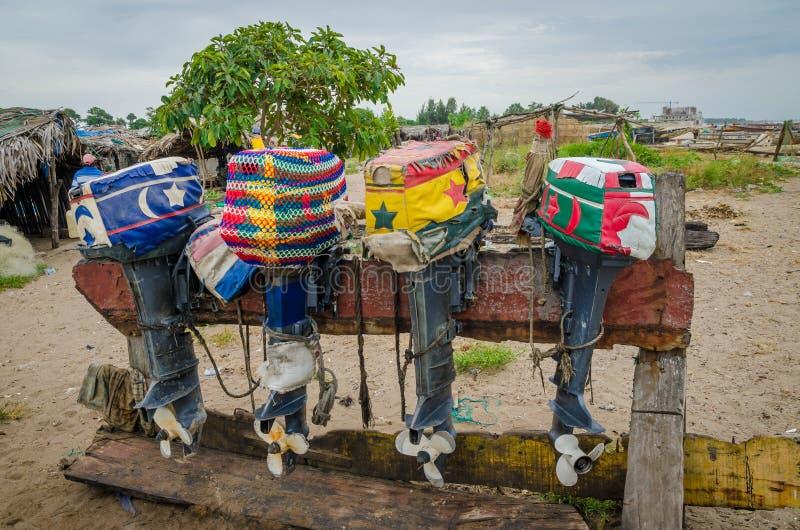 Moteurs alignés colorés de bateau de pêche avec les couvertures artistiques sur le support en bois, Gambie, Afrique de l'ouest photos libres de droits