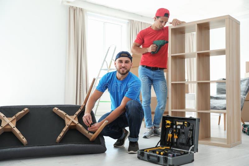 Moteurs masculins assemblant des meubles images stock