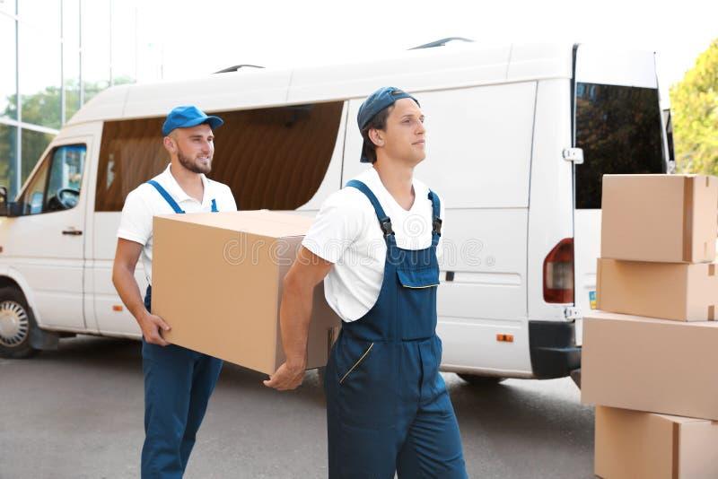 Moteurs masculins déchargeant des boîtes de fourgon photo stock