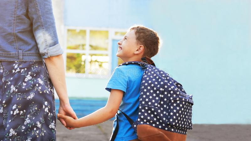 Mother accompanies the child to school. mom encourages student accompanying him to school. a caring mother looks tenderly at her. Mother accompanies the child to stock photos