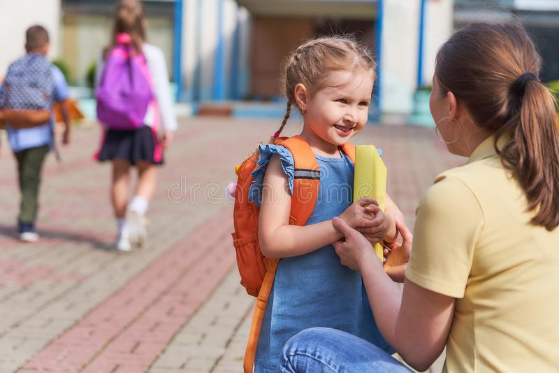Mother accompanies the child to school. Mother accompanies child to school. mom supports and motivates the student.caring mother with tenderness looks at her stock images