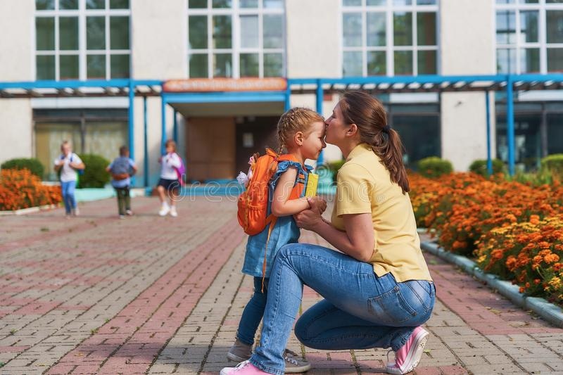 Mother accompanies the child to school. Mom supports and motivates the student.caring mother gently kisses her daughter on the forehead. positive little girl stock photography