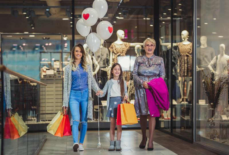 Mother, adult daughter and granddaughter in shopping mall royalty free stock photos