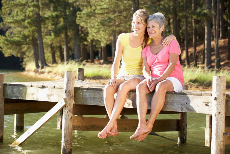 Mother and adult daughter sitting by lake royalty free stock photo