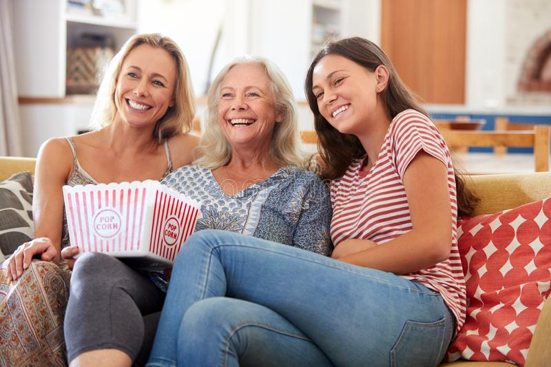 Mother With Adult Daughter And Teenage Granddaughter Eating Popcorn Watching Movie On Sofa At Home stock images