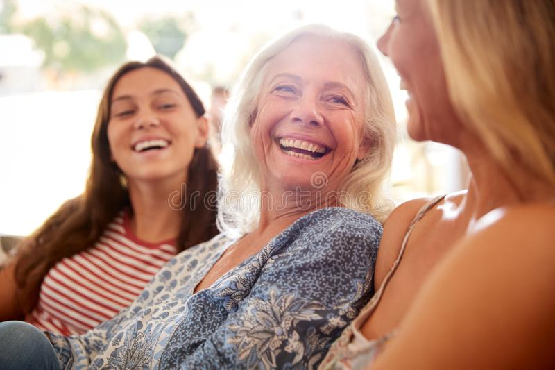 Mother With Adult Daughter And Teenage Granddaughter Relaxing On Sofa And Talking At Home stock photography