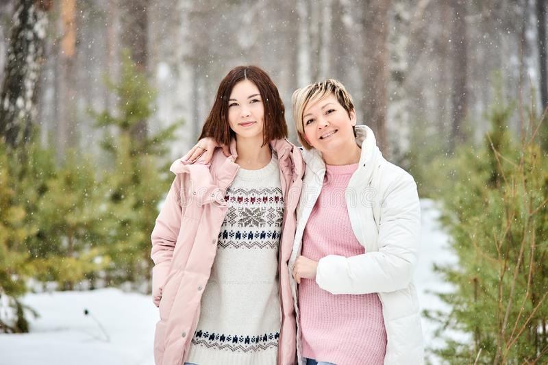 Mother and adult daughter walking in winter forest snowfall stock photos