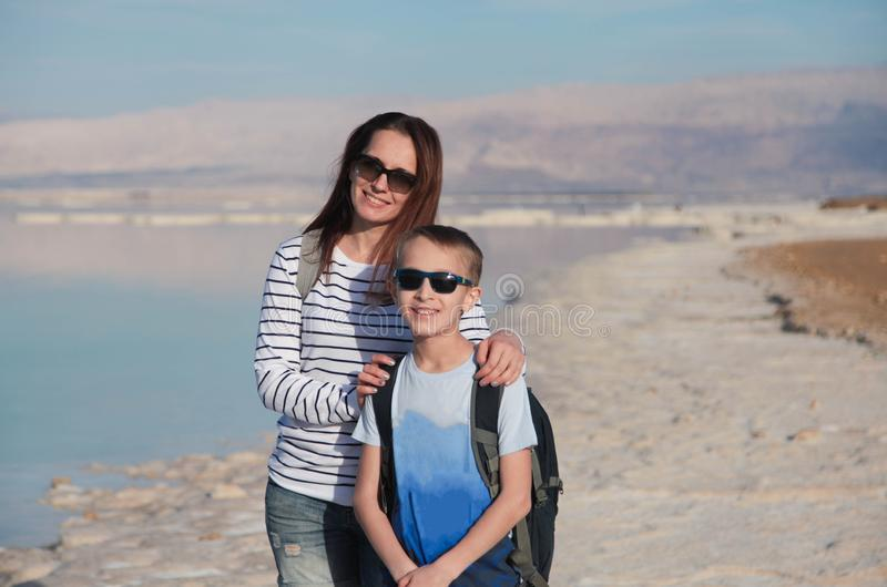 Mother ans son enjoying bright day on Dead sea beautiful salt shore. Israel stock photo