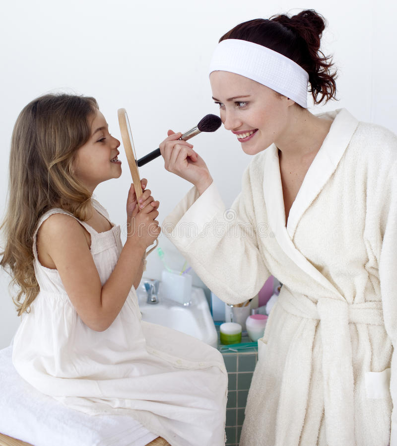 Mother applying blusher with her daughter stock images