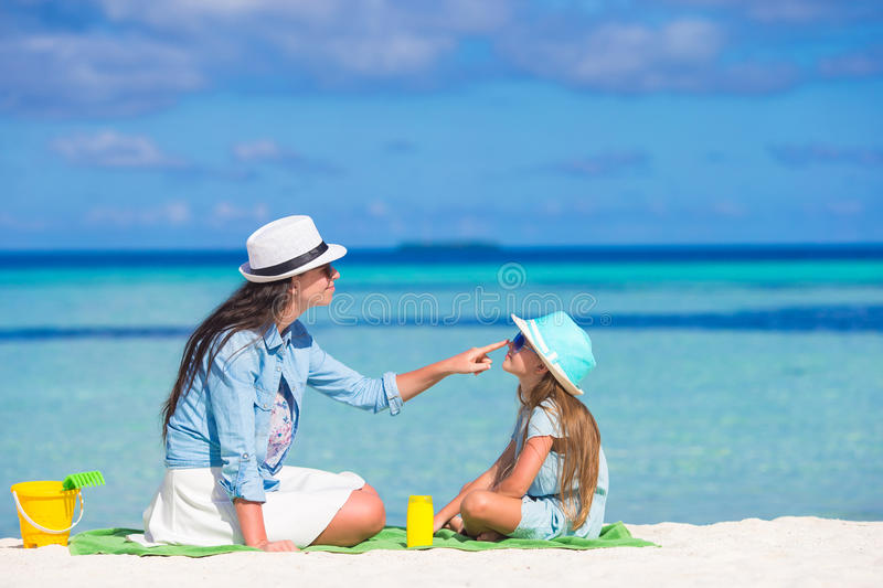 Mother applying sun protection cream to her stock photos