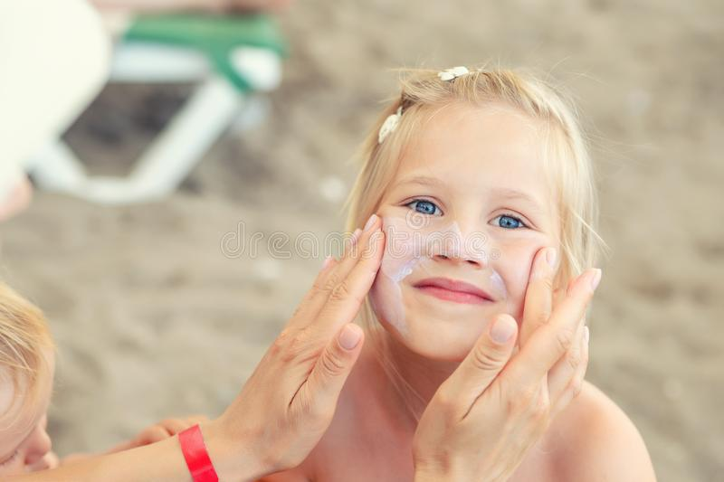 Mother applying sunscreen protection creme on cute little daughter face. Mom using sunblocking lotion to protect kid girl from sun. During summer sea vacation royalty free stock photos