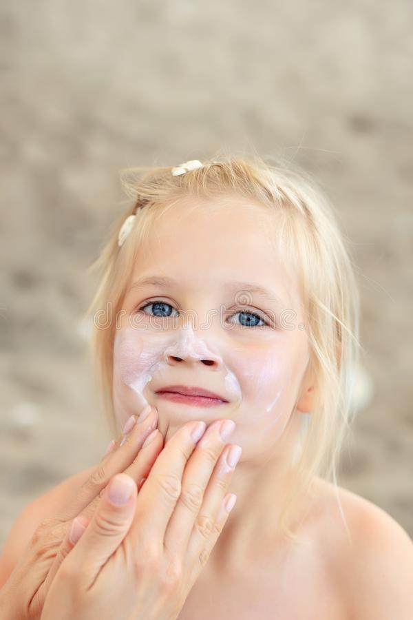 Mother applying sunscreen protection creme on cute little daughter face. Mom using sunblocking lotion to protect kid girl from sun. During summer sea vacation stock photo