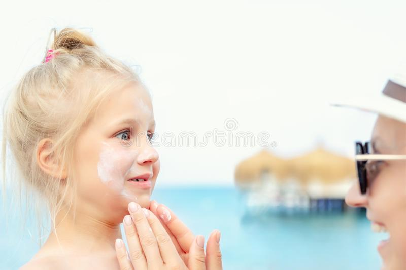 Mother applying sunscreen protection creme on cute little toddler boy face. Mom using sunblocking lotion to protect baby from sun. During summer sea vacation royalty free stock images