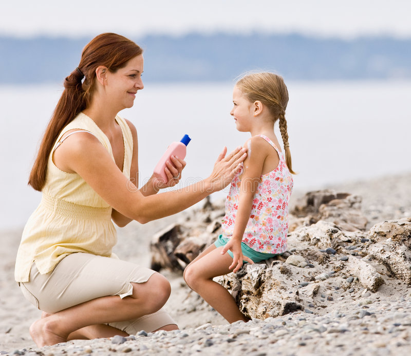 Mother Applying Sunscreen To Daughter At Beach Stock Images