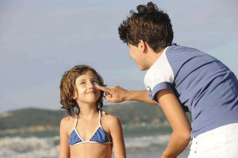Mother applying sunscreen to daughter at beach. stock photography