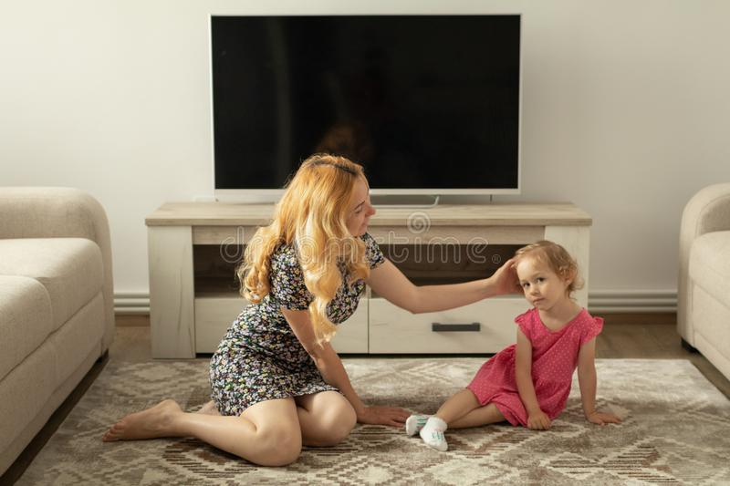 Mother asks little girl about her knee pain It hurts stock photo