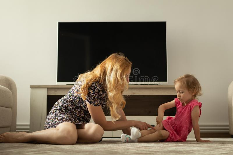 Mother asks little girl about her knee pain. It hurts. Mother asks little girl about her knee pain royalty free stock photo