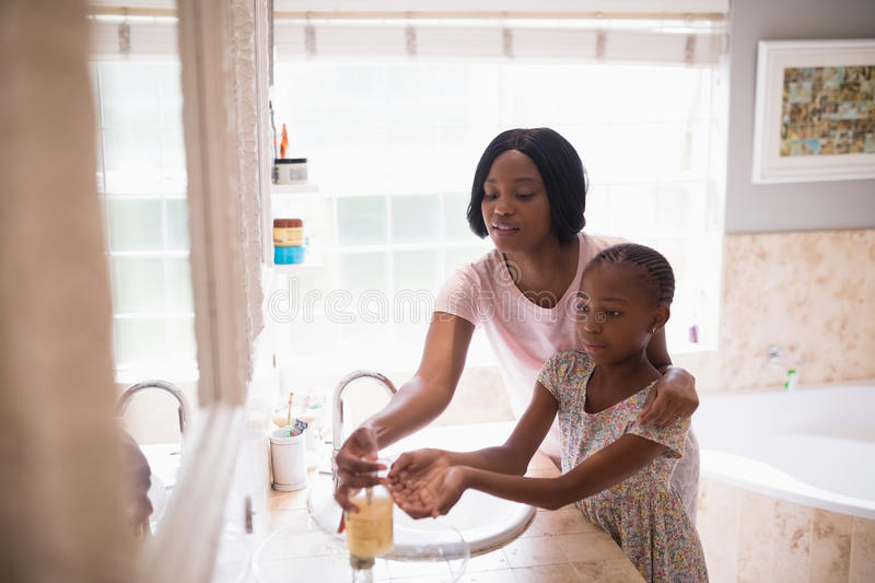 Mother assisting daughter while washing hands in bathroom royalty free stock image