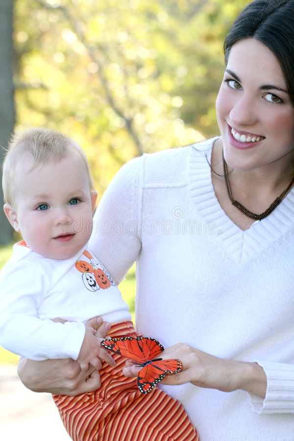 Mother and Baby Boy with Butterfly - Fall Theme. Portrait of a young mother and her blue-eyed baby boy with bright orange and red butterfly, outdoors in a park stock images